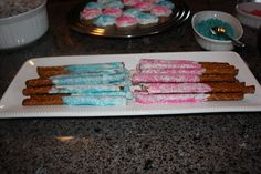 White Chocolate covered pretzel sticks with blue or pink sugar.