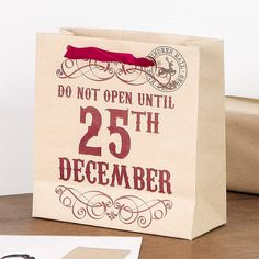 Do Not Open Until 25th December Small Christmas Gift BagAvailable as; Single Gift Bag £2.00 Two Gift Bags £3.95 (saving £0.05!) Four Gift Bags £7.00 (saving £1.00!) Six Gift Bags £9.00 (saving £3.00!)Wow, what a beautiful way of presenting a gift this festive period - it is those little finishing touches that make all of the difference. This fantastic quality gift bag is made from recycled robust card with a rigid base and Christmas red satin ribbon handles. Complete with round message tag…