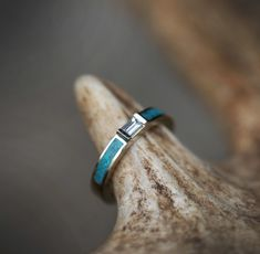 Each of our rings is a handcrafted one-of-a-kind piece, and is made to order for you and your significant other by a passionate and skilled artisan. Pictured is a silver engagement ring with a white sapphire center stone and hand-crushed turquoise inlay.  The width of the ring pictured is approximat