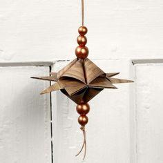 Den Stern fast wie den klassischen Flechtstern flechten - Unterschied: die vier Sternspitzen auf beiden Seiten wie eine Pyramide flechten. Er hängt horizontal statt vertikal. Das dünne Lederband ist mit mit Art Metal Farbe bemalten Holzperlen verziert.