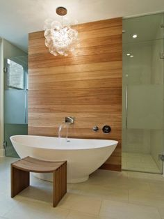 """In this contemporary master bath, the warmth of natural wood balances the stark elegance of the freestanding tub, for a look that's sleek and sophisticated. """"The simplicity of the materials and layout gives the occupant a calming sense when in the space,"""" says architect Steve Besch. """"The clean cedar wall is a relaxing backdrop to the freestanding tub and decorative light fixture."""""""