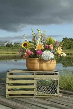 Nantucket inspired #arrangement with a basket of fresh flowers placed atop a lobster trap.