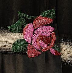 BEADED SATIN EVENING DRESS, 1920's. Sleeveless black silk having ombreed bands of black, grey and white beads, two at drop waist and one near hem, with red, pink and green beaded roses.