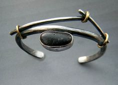 "Bracelet | Patricia McCleery. ""Twig Pebble""  Lake Michigan beach pebble set in silver, with accents of gold."