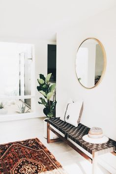 entry way // circle mirror // black and wood bench // potted plant // living room