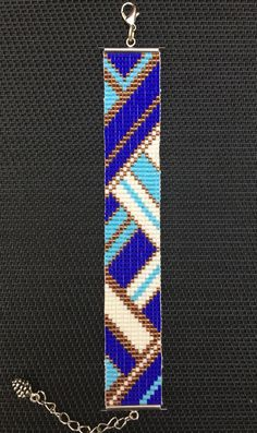 Cuff Bracelet woven beads Miyuki (Japanese glass beads)  Reasons graphic and geometric inspired turquoise blue electric blue coloured white and bronze.  Making handmade by my care Fixing silver with a charm metal Pine Cone  Size 14 cm Strap 2 cm width adjustable 5 cm more Ideal for a 15-19 cm wrist  Do not put in contact with liquid Avoid putting perfume  ///////////  Bracelet with miyuki delica beads  Geometric design inspired with blue, white and bronze colors  Hand made by me ;)!  size…