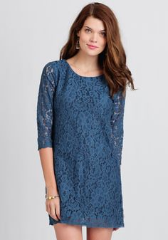 A vibrant, saturated blue, floral lace overlay decorates this stunning dress featuring a shift silhouette and three-quarter length sleeves.