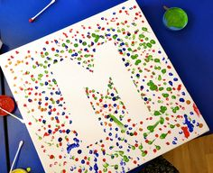 group art projects for preschool; lay teacher initial down on canvas, have each student pick a color, dip in pencil eraser, and do 10-15 dots all over.
