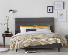 Curate a modern bedroom with the Tambur bed. The tall headboard and tapered legs inspire visions of the best design age. Featuring a platform-style frame, there is no need for boxsprings. Chic charcoal grey upholstery envelops the frame and complements the solid wood legs. Purchase online at SCANDIS.com