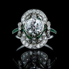 Edwardian diamond ring features a 1.80 carat sparkling European cut diamond set in a semi-bezel surrounded by small accent diamonds and calibre cut emeralds with adorable bow motif shoulders. Pristine Condition.The Gemstones are described as follows:One European Cut DiamondWeight: 1.80 caratsColor: IClarity: VS2Fifty Four Round Cut DiamondsWeight: .75 carat total weightColor: H-IClarity: VS-SIThirty Four Calibre Cut EmeraldsWeight: .30 carat total weight
