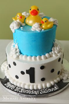 Rubba-Dub Dub #21Milestones  This design is a two-tier round iced in buttercream and features polka dots on the bottom tier. The top tier includes bath bubbles and is topped with plastic duckies toys.
