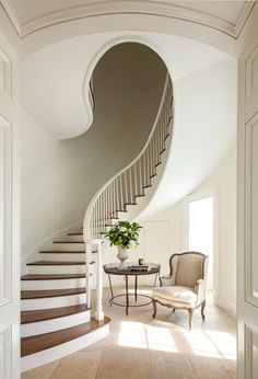 An elliptical stair rises to the second floor.