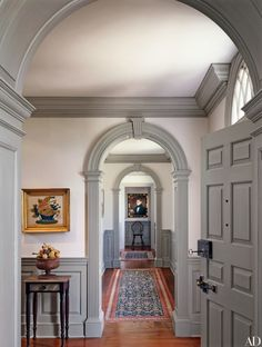 A gallery off the entrance hall of this New Jersey home features a number of artworks, adding personality to the narrow space | archdigest.com