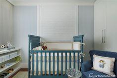 Berço de bebê com enxoval branco e bege e ursinho, papel de parede azul e bege.