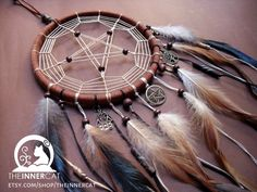 TheInnerCat's Moon Howling Wolf Dream Catcher (Handmade) SOLD --> www.etsy.com/shop/theinnercat The Charm has the Moon, Wolf and a feather on the side. The pattern on the dream catcher symbolize...
