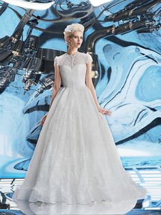 Venus from the Sky Collection by Helen Miller Bridal. A romantic wedding gown with a beautiful lace cap sleeve and illusion front,  this dress is perfect for the bride who wants a bit more coverage.