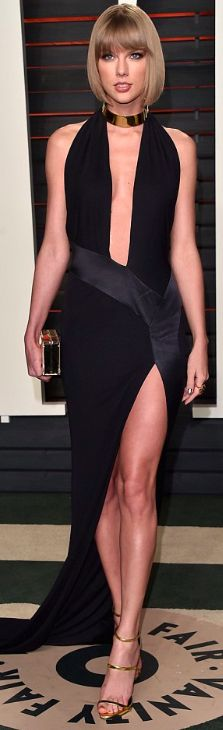Taylor Swift's floor length frock featured a very low cut neckline and a thigh high split as well as a train. Still rocking her fringe bob, the multi-awardwinning singer stood tall in a pair of gold heeled sandals.