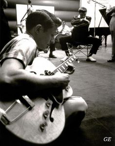 Great picture of Scotty Moore playing as Elvis listens intently in the back ground. Scotty is best known for his backing of Elvis Presley in the first part of his career, between 1954 and the beginning of Elvis' Hollywood years.