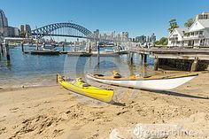 Two kayaks on the beach at Lavender Bay with the harbour bridge and city in background. Copyspace.