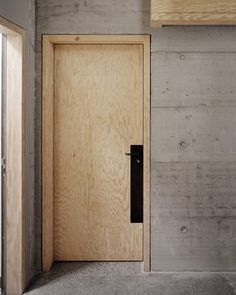 light unfinished wood door + concrete walls + deep black contrast on accessories
