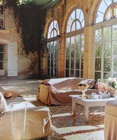 Chateau Sun Room, Burgundy, France -- I love the idea of a casual sun room. The tiles are gorgeous as are the large arched windows encased in stone.