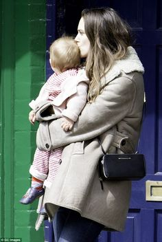Out and about: Keira Knightley was seen planting a tender kiss on her daughter Edie's head...