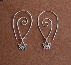 Earrings sterling silver lotus charms and hammered spiral sterling silver ear wire. 28.00, via Etsy. by tania