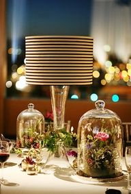 floral arrangements under glass cloches, and lamps with black and white striped shades