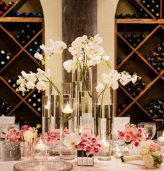Phalaenopsis orchids in tall clear vases with smaller bouquets around