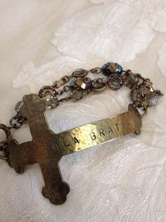 hand hammered and stamped cross bracelet, with Latin inscription and vintage swarovski bezels, chain and caps...