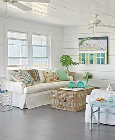 lovely coastal white beadboard clad walls, white sofa, wicker trunk as a coffee table and pops of green and aqua for a coastal nautical style...love too the colonial feel to the white fans x