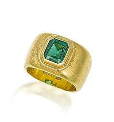 An emerald ring, by Grima  The rectangular step-cut emerald collet-set within a raised surround, to a square mount of engraved decoration, signed Grima