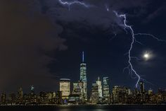 "Picture of lightning striking over lower Manhattan    ""Lightning strikes lower Manhattan as a summer storm approaches a moonlit New York City skyline.""—Christopher Markisz"