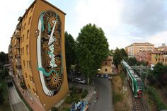 """Polish artist, Mariusz Waraz, akaM-City, has just completed this large mural in Bologna, Italy for an event titled """"Frontier."""" This piece is another one of the artist's mechanical/architectural visions, consisting of an immense amount of detail and a giant crank."""