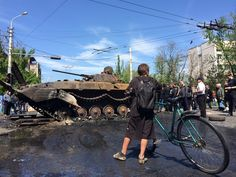 civilian bike usage in Ukraine: A boy with a bicycle stops to look at the smoldering ruins of a Ukrainian armored vehicle in central Mariupol on May 10.