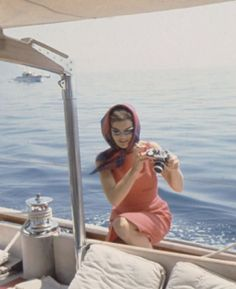 Jackie Kennedy Onassis on a boat with a camera
