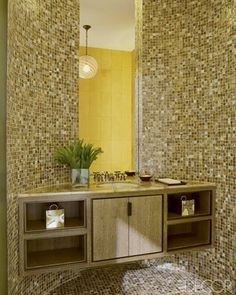 For a film director's New York City loft, interior designer David Kleinberg created a circular powder room sheathed floor to ceiling in glass mosaic tiles from Walker Zanger. The marble-top wenge vanity has a sink by Vitraform and fittings by Waterworks.   - ELLEDecor.com