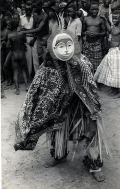 Nigeria, adult [male?] wearing Ibo masquerade costume including patterned cloths, reeds, rattles [?] around ankles, round mask [painted wood?] with feathers on top. Male possibly dancing. Crowd of male adults and children, some wearing cloths, some wearing American clothing, looking on in background. Outdoor setting. Medium: Gelatin silver print. Format: Photograph slotted into dark brown paper mount. Appears to have been used as Christmas card.