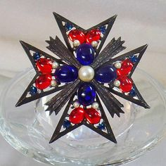 This #vintage Weiss Maltese cross brooch pendant is just incredible!  It features a dark metal rustic Maltese cross with bright red and dark blue oval cabochons, blue rhines... #ecochic #etsy #jewelry #jewellery