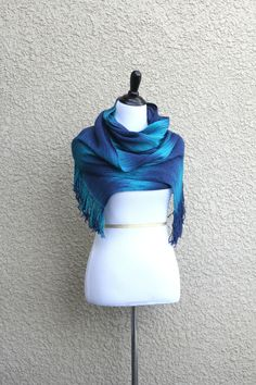 """Hand woven long scarf with gradually changing colors from dark blue to turquoise. Measures: L: 78"""" with 6"""" fringe on both ends W: 11"""" Care instructions: This scarf made with a 100% Merino Superwash Wo"""