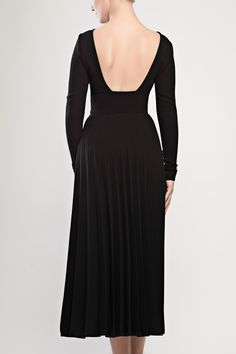 Pleated crepe dress with open back. This black gown is a sexy modern classic. Designed from heavy yet fluid crepe, this elongating design has extra long sleeves with fabric covered buttons and an alluring open back.