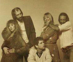 John McVie playfully choking Christine, a nonplussed Lindsey & Stevie & Mick