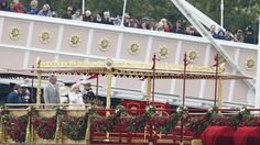Queen Elizabeth II, centre, points down river while standing on the royal barge, the principal boat of a flotilla of 1,000 vessels, on the River Thames, during a river pageant to celebrate the Queen's Diamond Jubilee in London on Sunday, June 3, 2012. (AP /Matt Dunham-Pool)