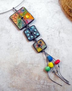This necklace features a pendant of 3 tiles from polymer clay. They are textured, tinted with pastels and varnished. 4 matching little polymer clay