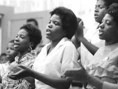 Young women singing a freedom song in a Selma, Ala., church. The mass meeting was held to raise spirits and recruit participants for a voter registration demonstration. In 1964, Matt Herron and a group of photographers documented the Freedom Summer in what he called the Southern Documentary Project.