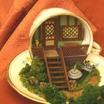 Quarter scale cabin porch in a tea cup exhibited at the Spring 2010 Seattle Dollhouse Show - Photo copyright 2010 Lesley Shepherd, Licensed to About.com Inc.