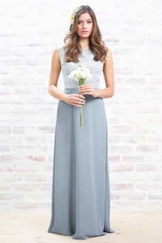 <ul> <li>Elegent, fitted bodice of ivory lace overlay with solid crepe skirt.</li> <li>Sleeveless, round neckline with scoop back.</li> <li>Inverted pleat detail at back of skirt waist.</li> <li>Skirt is A-line.</li> <li>Fully lined.</li> </ul>