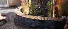 Hij geeft een romantisch sfeertje: deze tuinbank met kronkelende vorm. Hij dient niet alleen als muurtje voor de borders, maar je kan er ook nog eens lekker op zitten. Met héél veel vrienden.