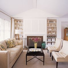 Fantastic white cream brown living room space. Love the cream tufted chairs and dark wood tray coffee table. Thanks to PCH! Great built-ins: shelves and cabinets and modern fireplace too. Wood tripod floor lamp, white cotton drapes and wool rug! Love white walls paint! White paint wall color! white cream beige brown purple living room colors!