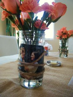 Bridal shower flower arrangement. Mason jars with pinkish-orange carnations and roses.